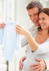 pregnant couple shopping for baby clothes